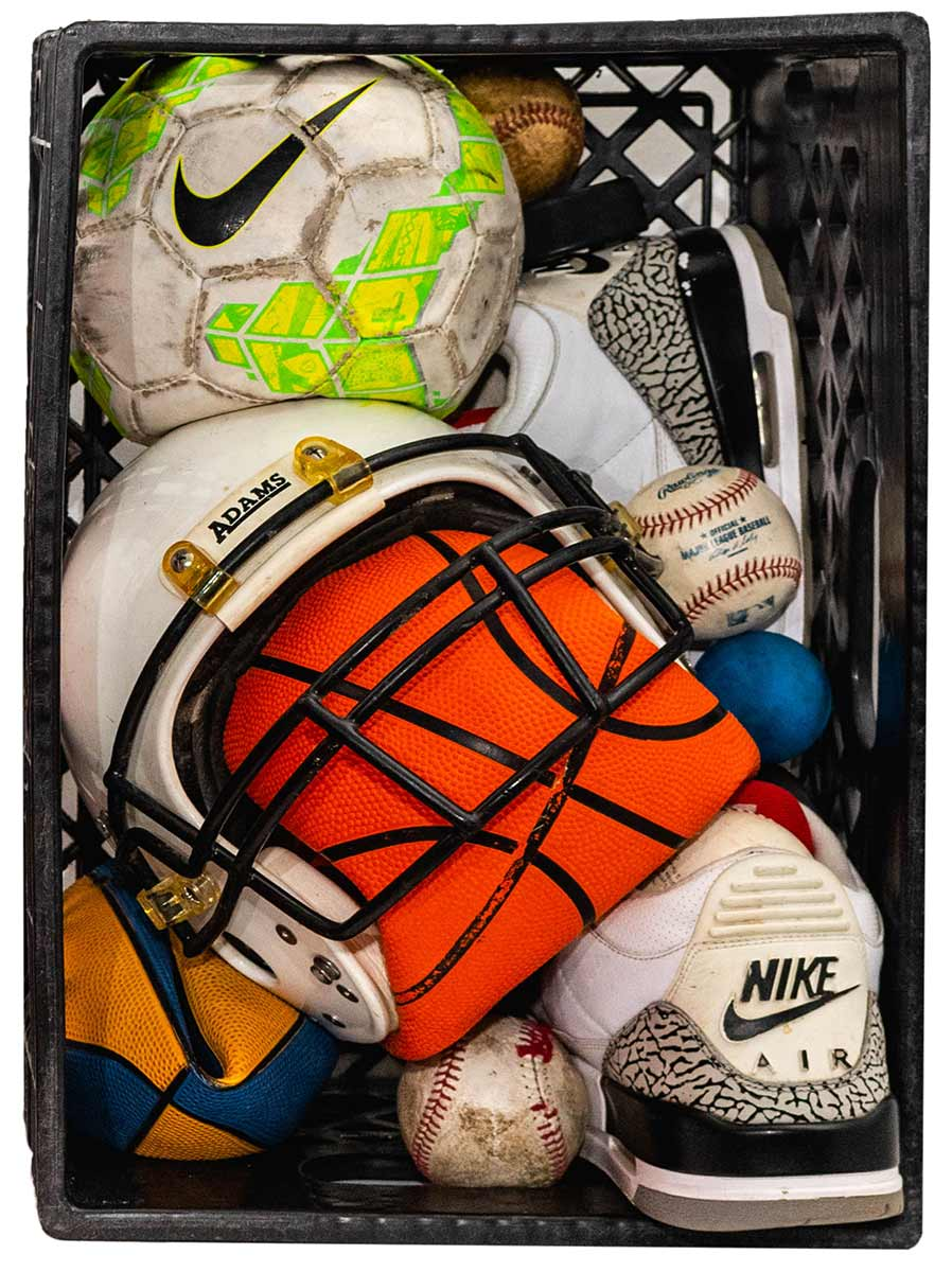 "Tyrrell Winston, ""Black Crate:From A to B and Back Again"", 2020, Found milk crate, used sports equipment, used tennis shoes, foam, liquid plastic, 13 x 19"" x 10.5 inches"